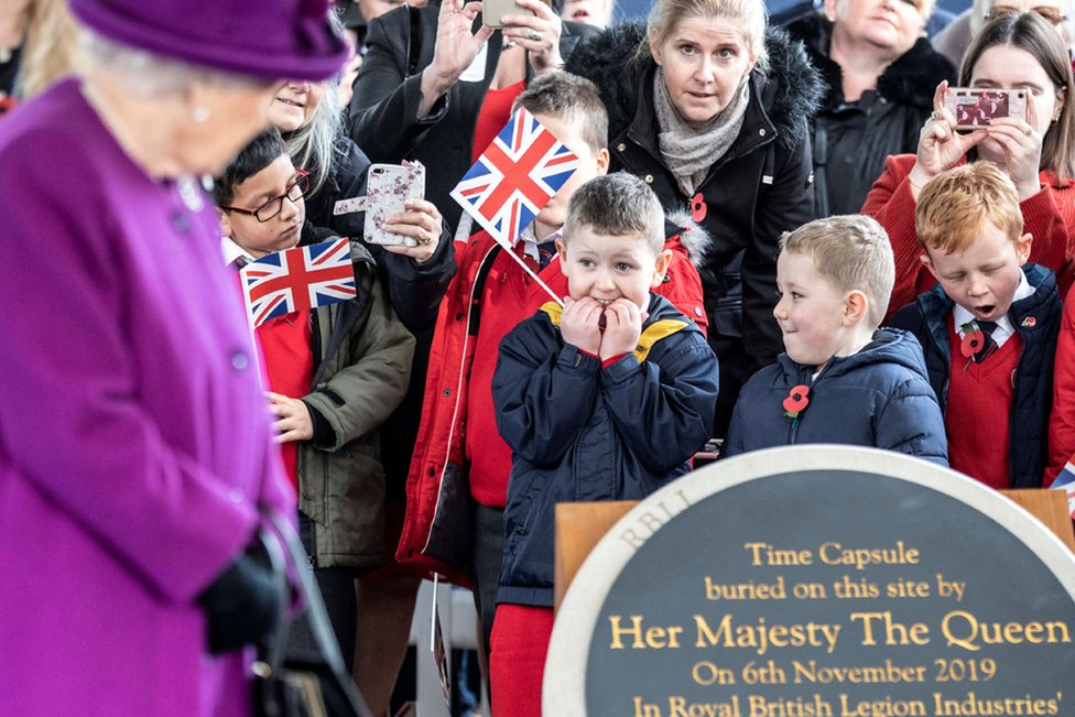 Children react as Queen Elizabeth II arrives to bury a time capsule at the Royal British Legion Industries Vllage in Aylesford