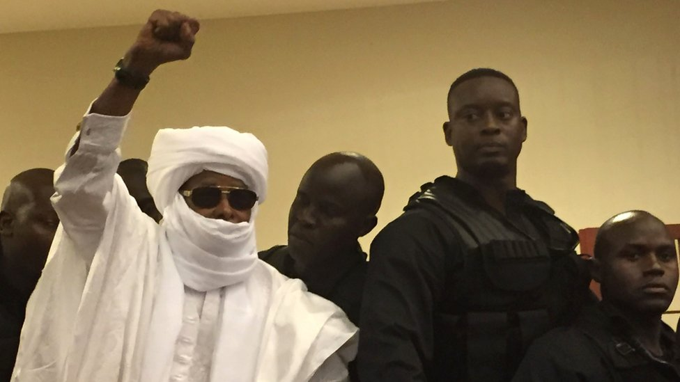 Hissene Habre raises his fist in the air during Monday's hearing