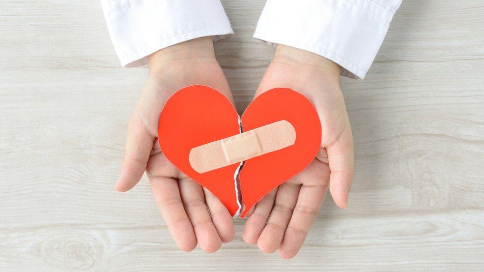 Unas manos con un corazón y una curita