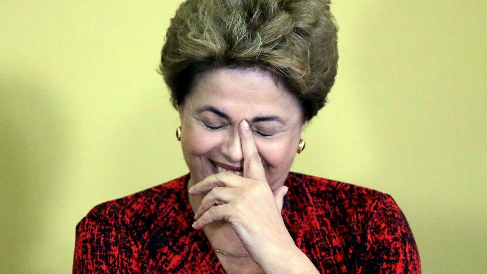 Dilma Rousseff laughing with her head in her hand, and her eyes closed