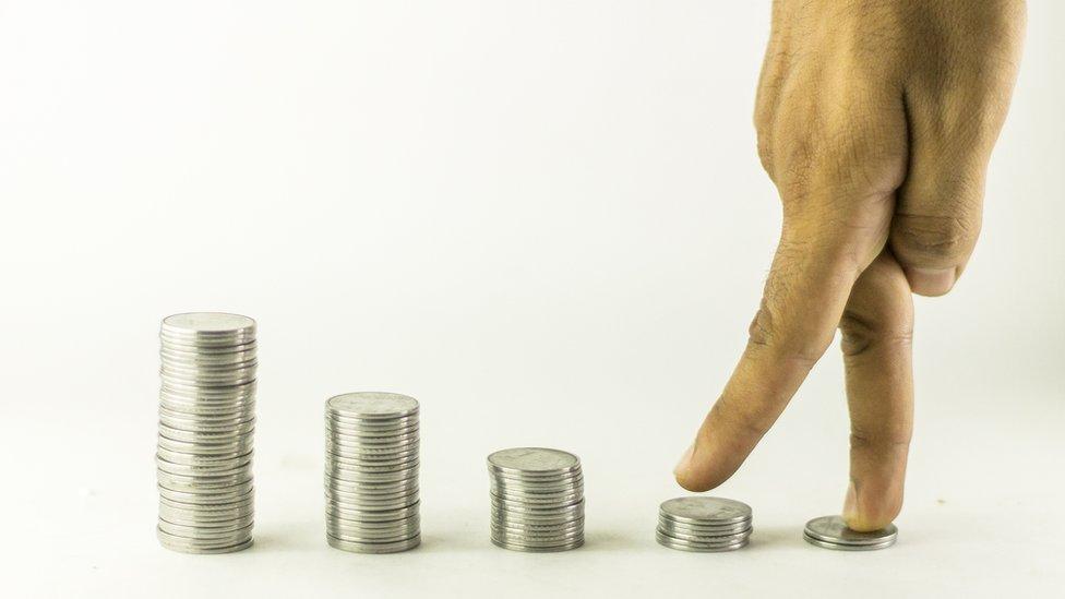 Dedos caminan sobre monedas en aumento.