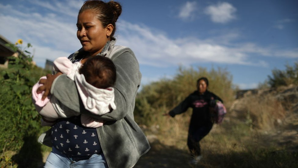 Una mujer inmigrante cruza el Valle del Río Grande con su bebé en brazos