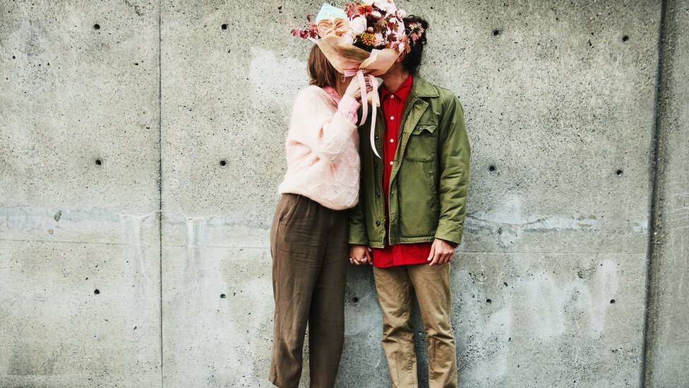 A couple kiss behind a bunch of flowers