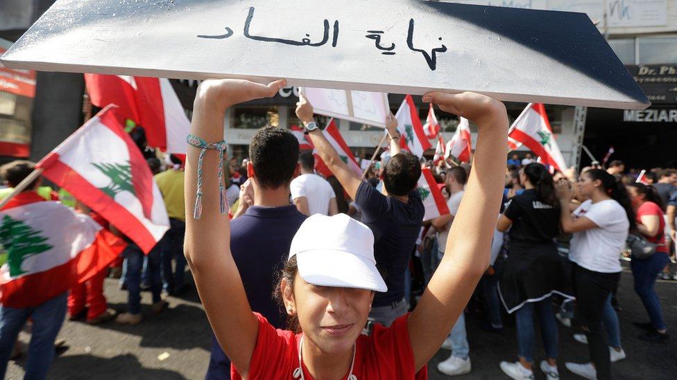 """متظاهرة تحمل لافتة كُتب عليها """"نهاية الفساد"""""""