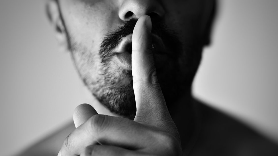 Man with finger against his lips