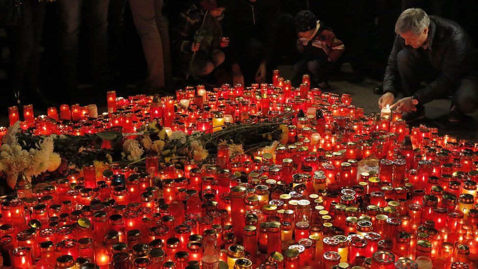 Romanian Prime Minister Dacian Ciolos (right) lights a candle for victims of the nightclub fire