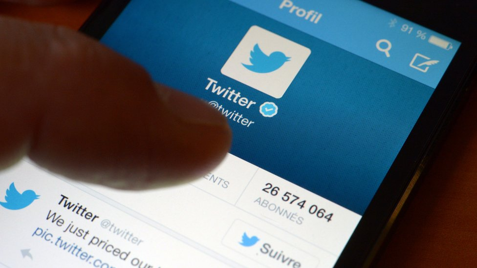 Thumb hovers over Twitter app on a smartphone