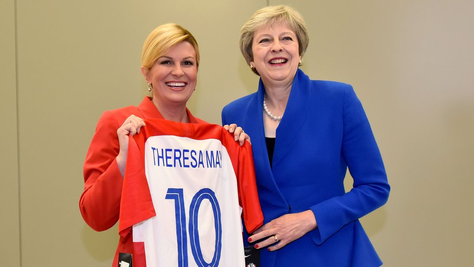 Croatia President Kolinda Grabar-Kitarovic (L) offering a Croatia national football team jersey to British Prime minister Theresa May (R) at the NATO headquarters in Brussels