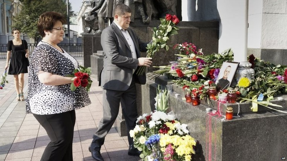 People lay flowers to the photo of Ihor Debrin - a national guard member killed on Monday