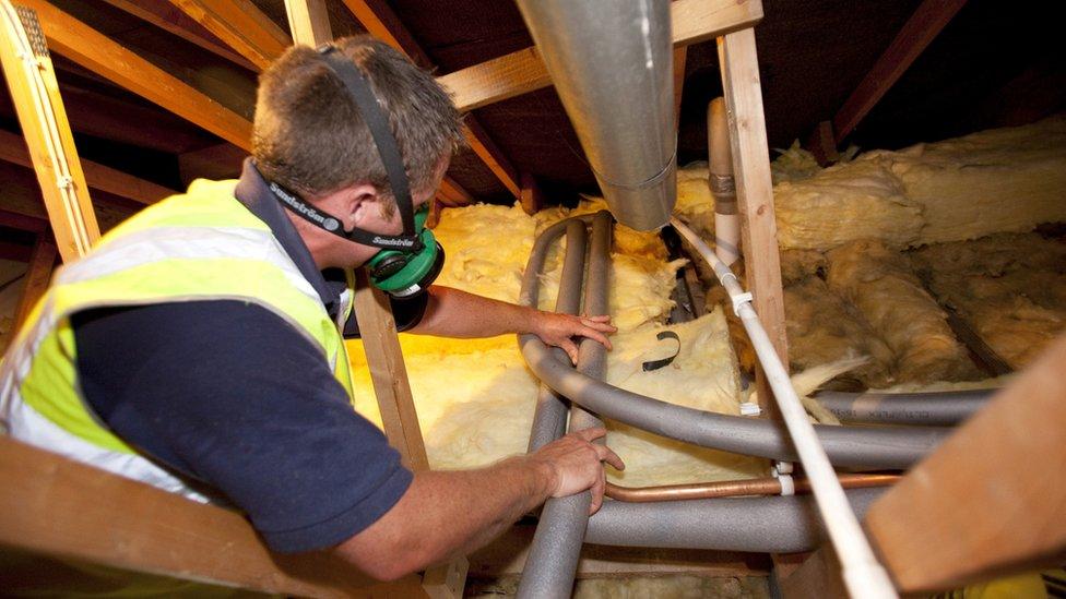 Worker installing loft insulation