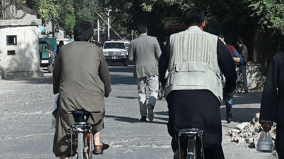 Homens de costas caminhando na rua