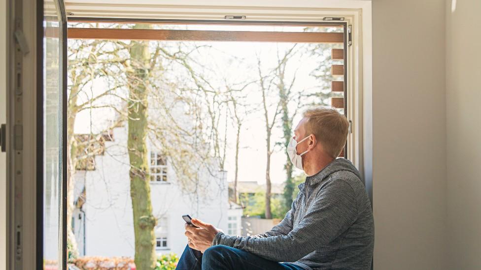 Hombre con mascarilla junto a una ventana abierta