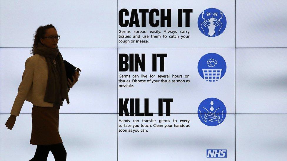 A woman walks past a public health information advertisement in London