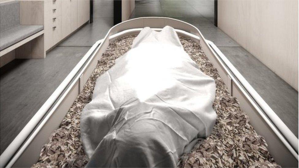Un cuerpo cubierto por una sábana sobre una cama de astillas de madera