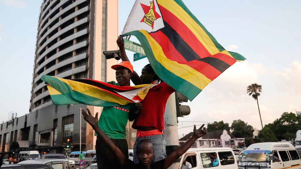 People holding Zimbabwean flags celebrate in the street after the resignation of Robert Mugabe as president on 21 November 2017 in Harare, Zimbabwe