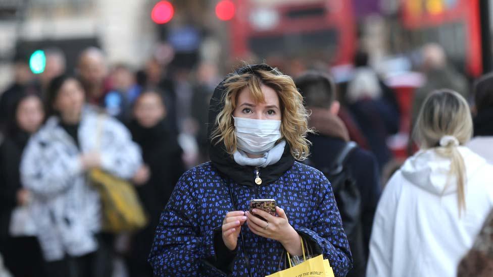 Una mujer usando una mascarilla en la calle en Londres.
