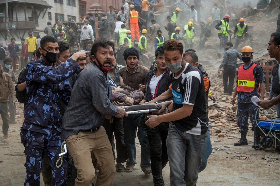 Emergency rescue workers carry a victim on a stretcher after Dharara tower collapsed in Kathmandu, Nepal