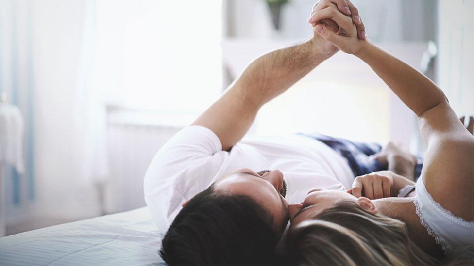 Una pareja acostada en una cama sujetándose las manos.