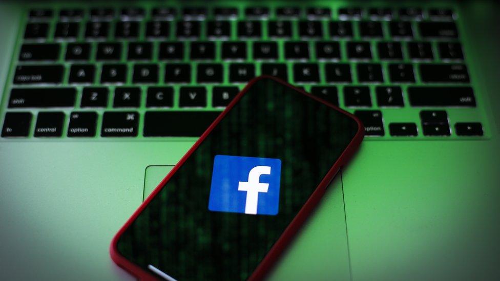 Ilustracija - logo Fejsbuka na ekranu telefona koji je postavljen na tastaturi