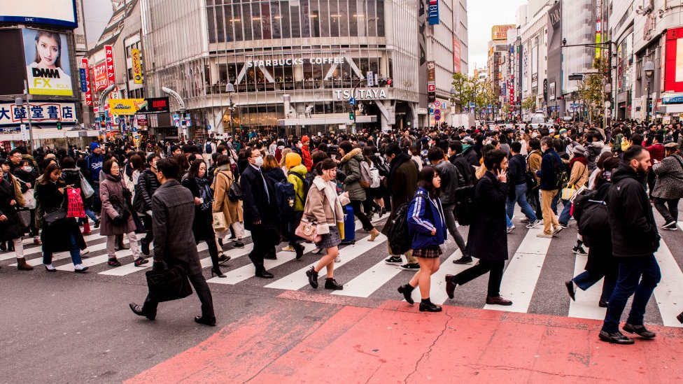 Gene cruzando la calle en Tokio