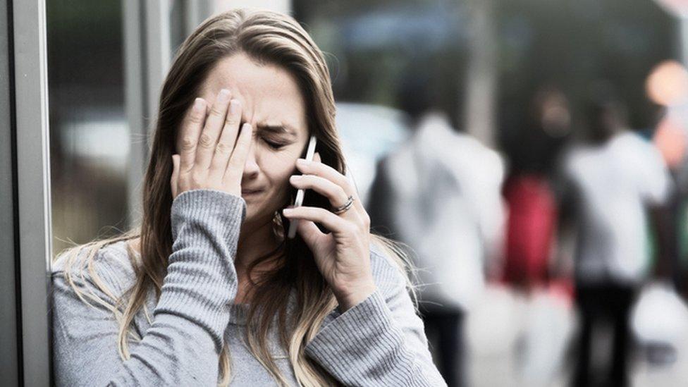 Una mujer se tapa la cara con un teléfono en la mano (imagen ilustrativa)