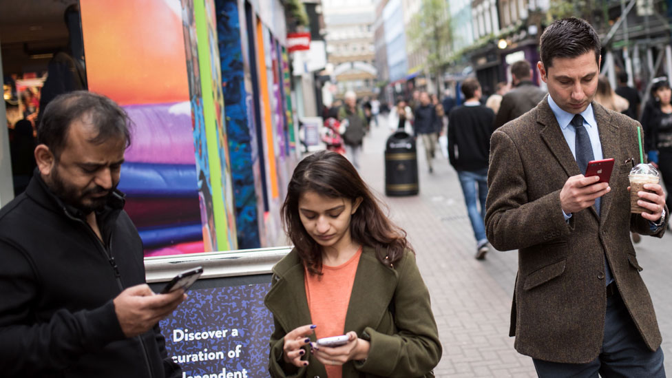 Shoppers look at their mobile phones