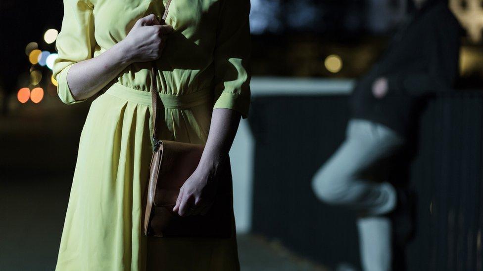 Women in dark with man watching her