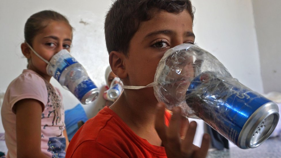 Children try improvised gas masks in their home in Syria's rebel-held northern Idlib province