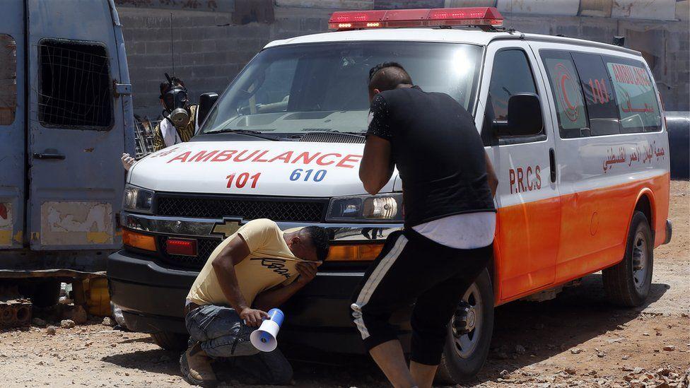 فلسطينيان يبكيان بجوار سيارة إسعاف
