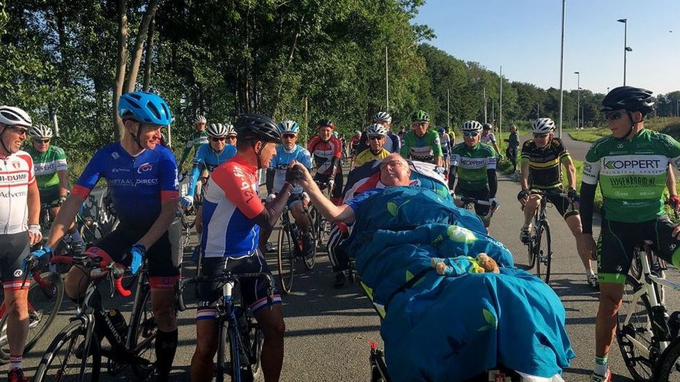 A terminally ill man is greeted by cyclists