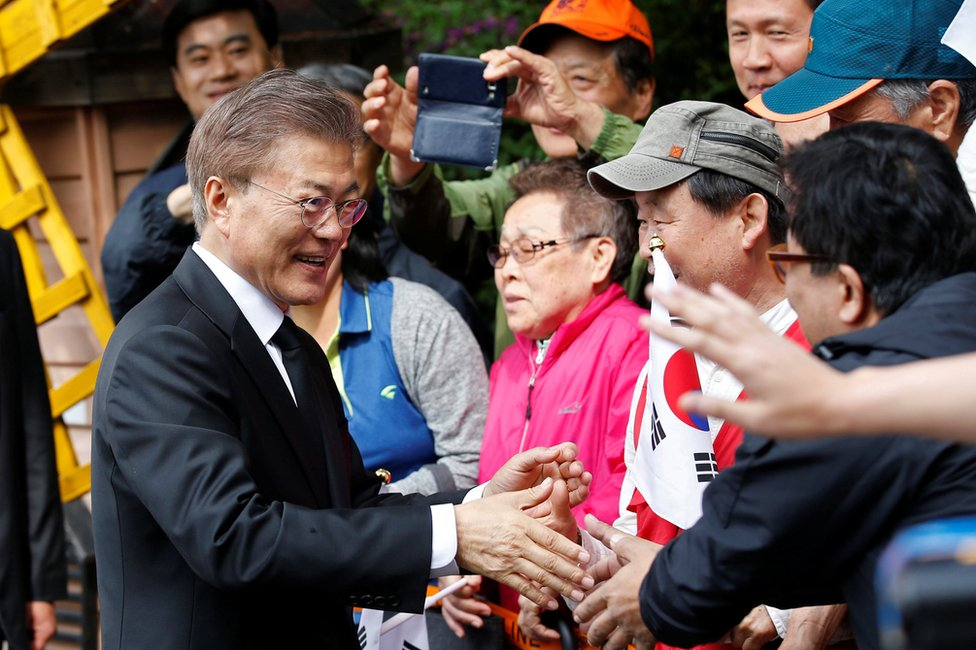 South Korea's President Moon Jae-in greets his supporters and neighbours as he leaves his house in Seoul, South Korea 10 May 2017