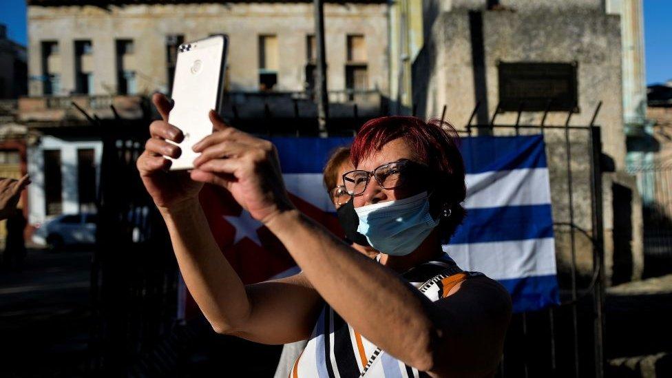 Mujer en Cuba con un teléfono celular.