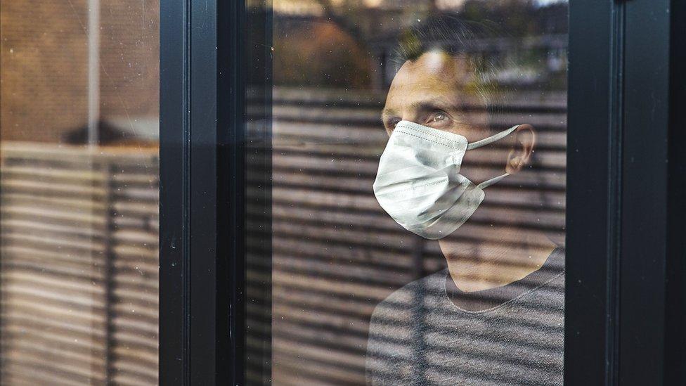 man in mask looking through window