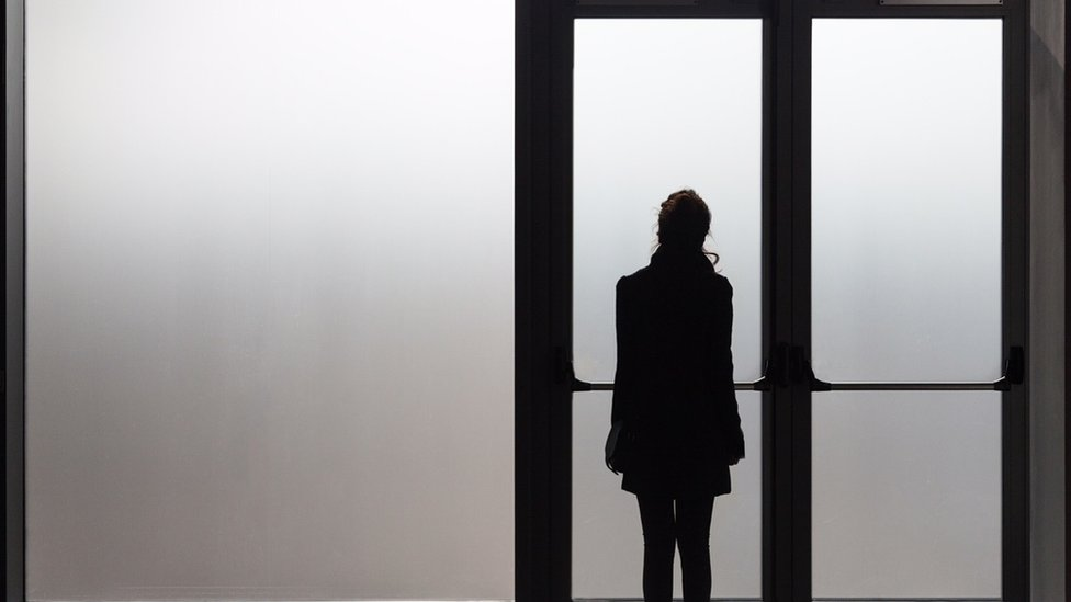 Mujer rmirando por ventana
