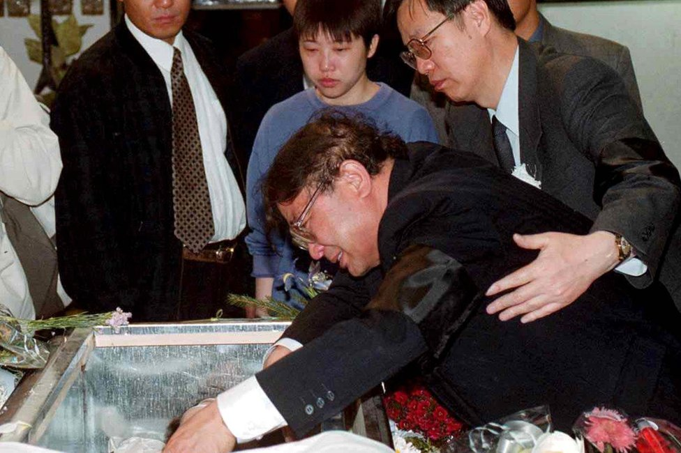 The father of Zhu Ying weeps over her coffin in Belgrade