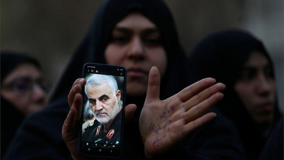 Mujer muestra foto de Soleimani en su celular