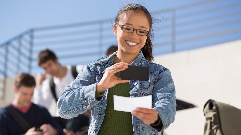 Una mujer fotografía un cheque.