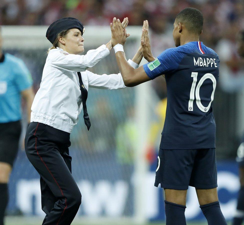 """Una de las """"intrusas"""" que accedió al campo de fútbol en la final de Rusia 2018 saluda a Mbappé."""