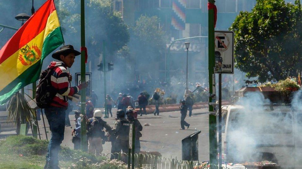 Homre con bandera de Bolivia y con gases lacrimógenos cerca