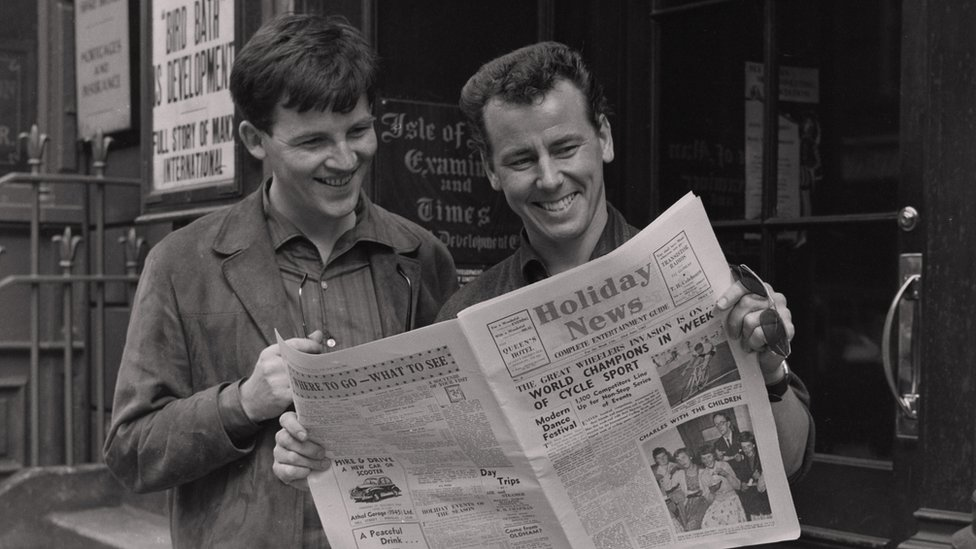 Black and white photograph of two men looking at a newspaper