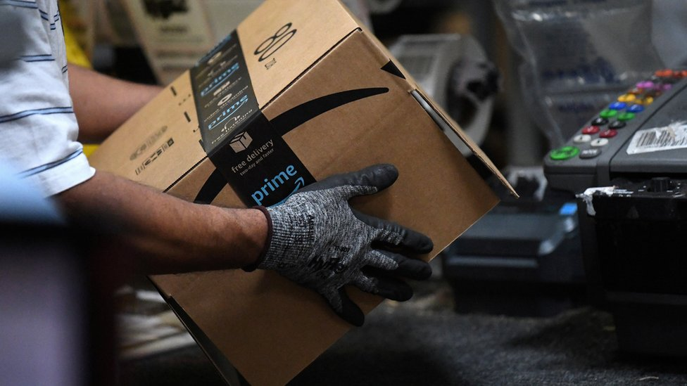 Worker assembles a box for delivery at the Amazon fulfilment centre in Baltimore, Maryland