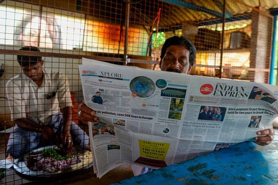 رجل يقرأ صحيفة فيها أخباراً عن جو بايدن ونائبة الرئيس كامالا هاريس في قرية أسلافها ثولاسيندرابورام في ولاية تاميل نادو جنوب الهند في 21 يناير 2021