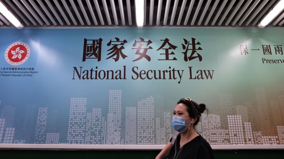A woman walks past a poster for the National Security Law in Hong Kong on July 28, 2020