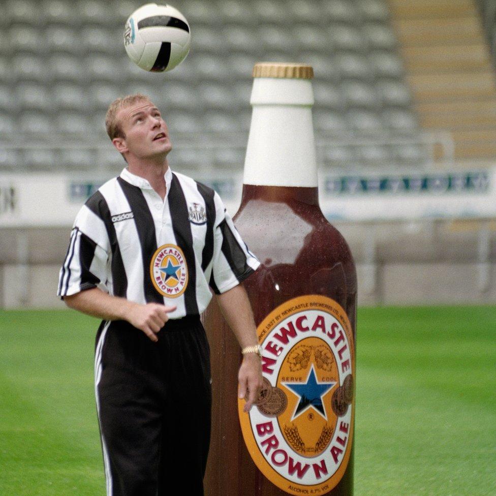 Alan Shearer heading a ball next to a giant Newcastle Brown bottle