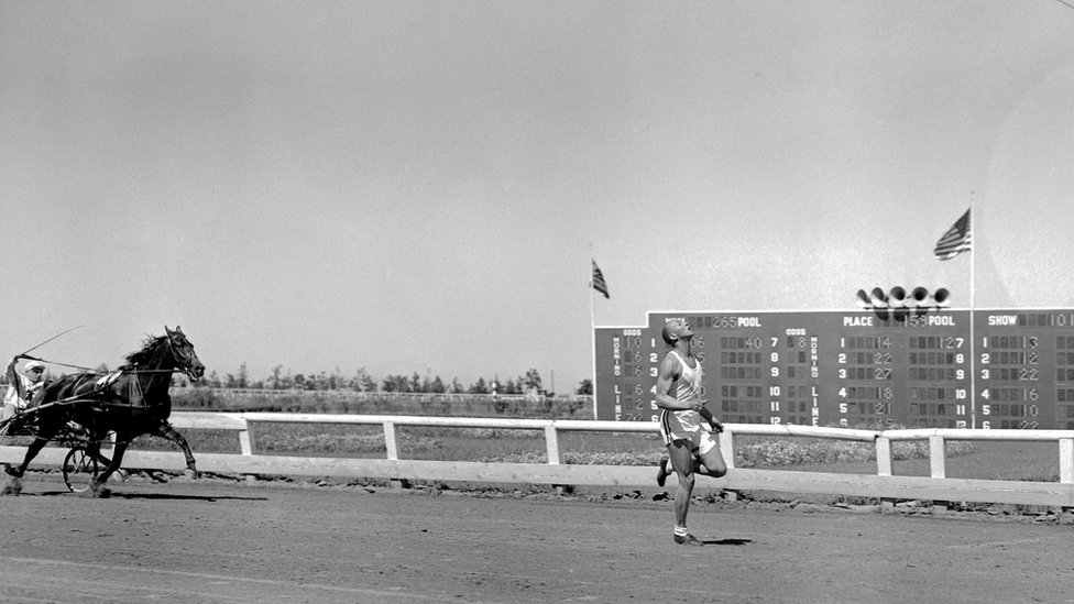 Jesse Owens seen sprinting ahead of a horse