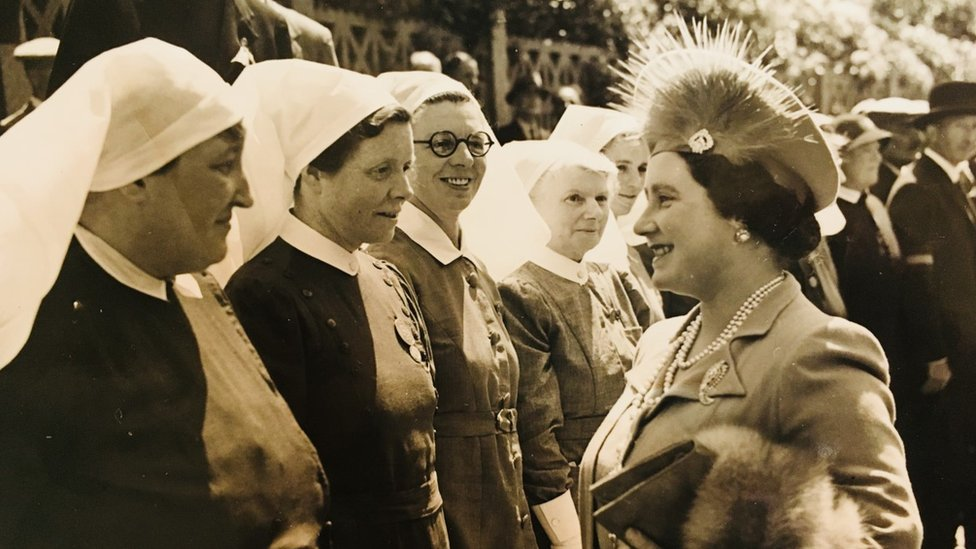Betty Thornley lined in a row meeting The Queen's Mother