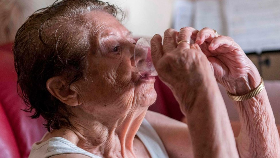An elderly person drinks a glass of water to avoid heatstroke and dehydration in Clermont-Ferrand - central France