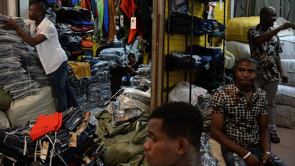 In a picture taken on August 26, 2013, Lamine Ibrahim (L) from Guinea works as his four-year-old son (back C) looks on at their shop inside a clothing wholesale market in Guangzhou