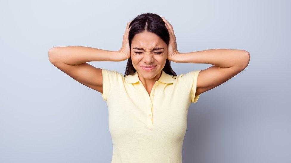 Mujer joven tapándose los oídos en señal de dolor.