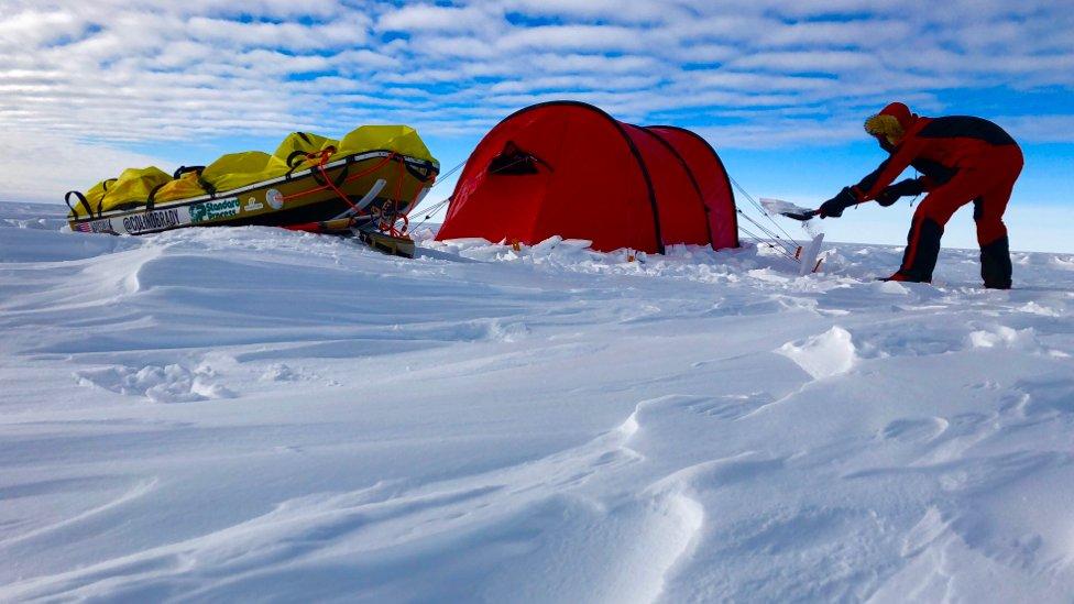 Colin O'Brady asegurando su tienda de campaña sobre la nieve y el hielo